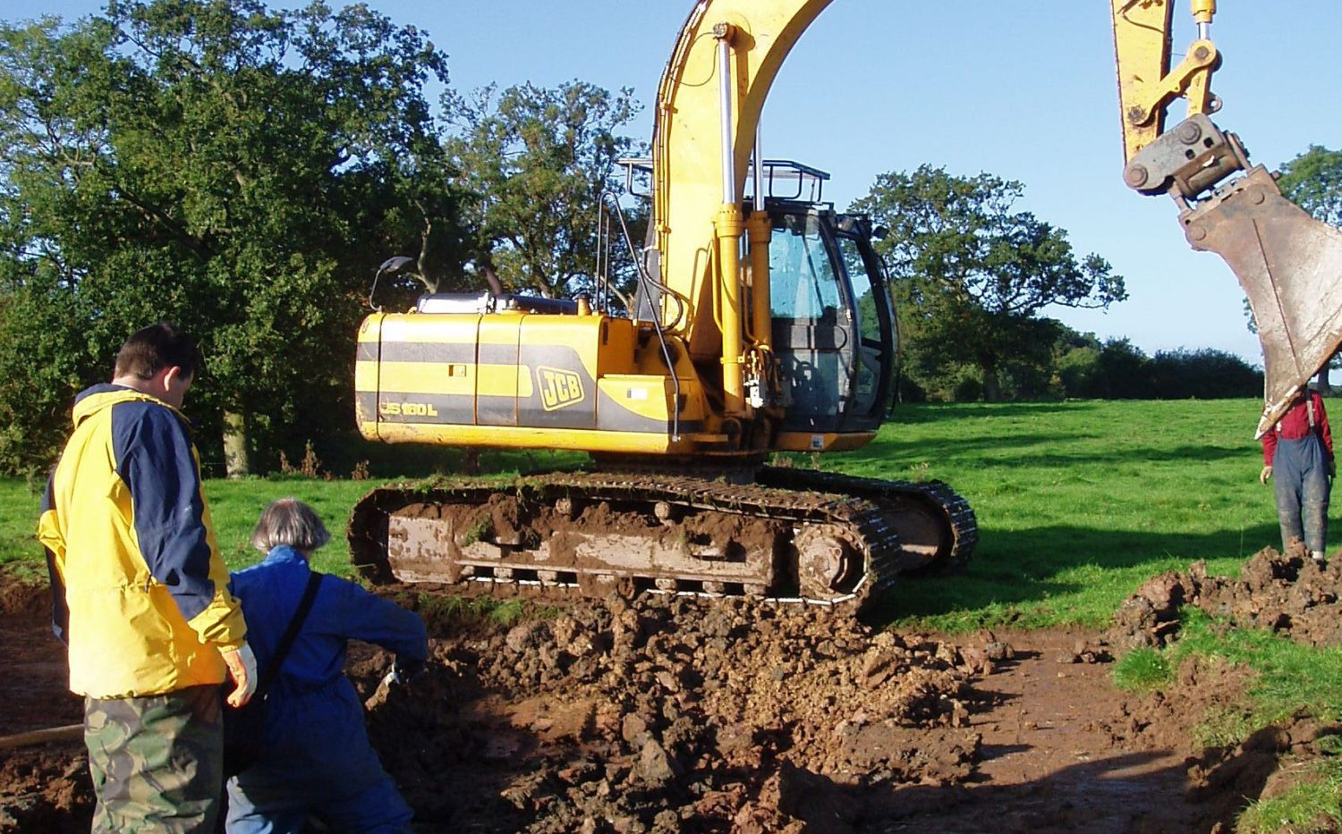 A very large excavator strips the turf