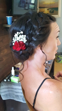 Brunette Bridal Updo with low braided bun and flowers