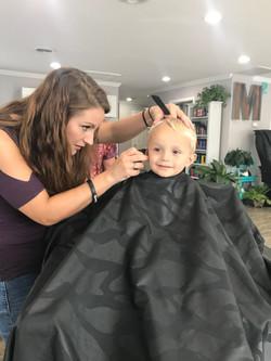 Stylist cutting boy's hair