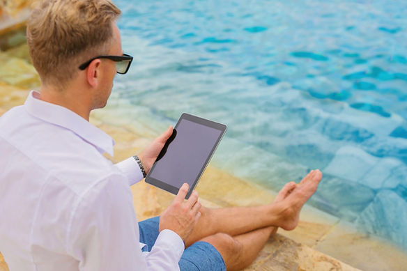 man-glasses-tablet-computer-by-the-pool-