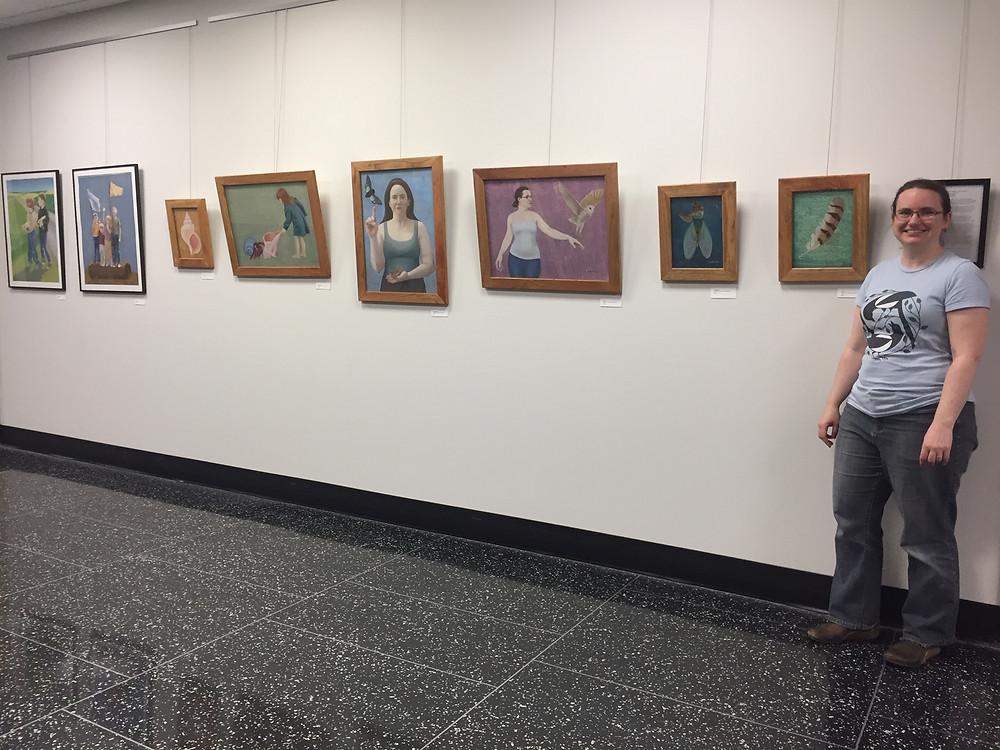 The artist stands next to a series of her paintings on display.