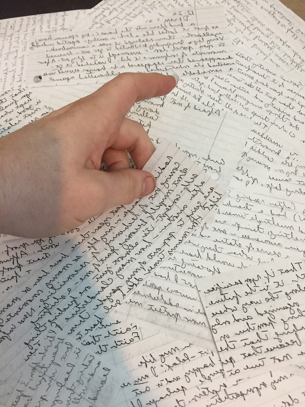 A hand places pieces of paper together that have handwriting on them.