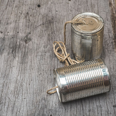 old tin can phone on wood texture board.