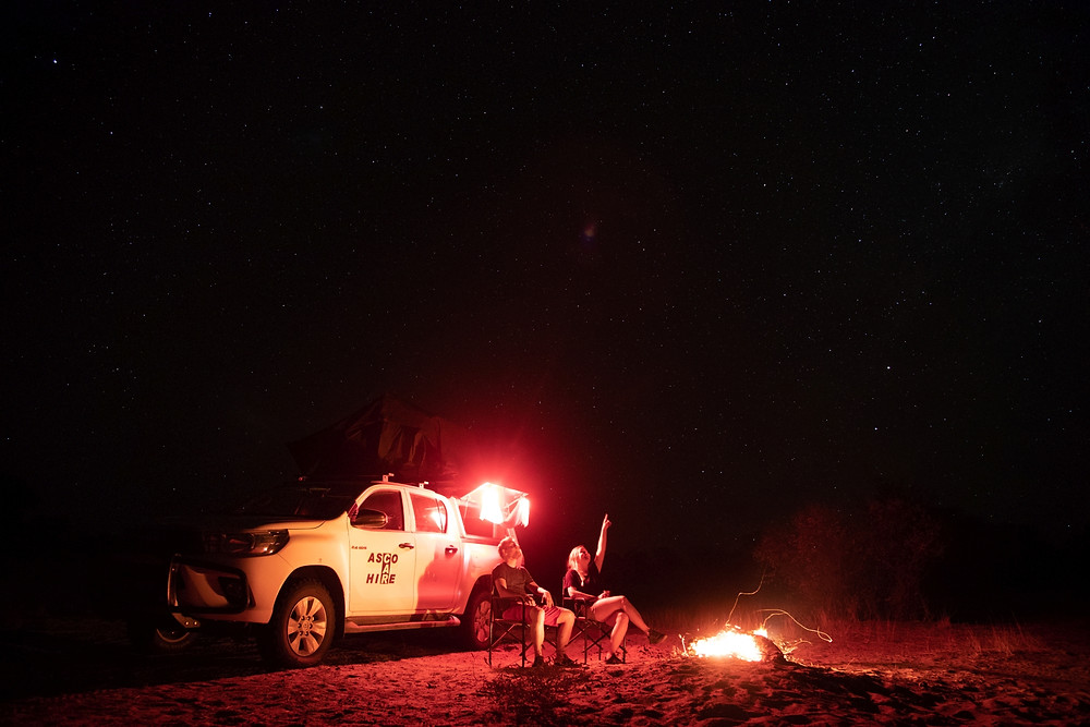 Couple sitting at a campfire looking at the stars