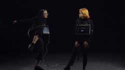 Emily and Georgina wear all black and have screens on their chests. They face eachother.
