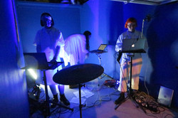 Emily, Georgina and Rubie are performing on laptops in a blue painted garage.