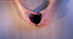 two female hands cupping a thermos cup on table surface