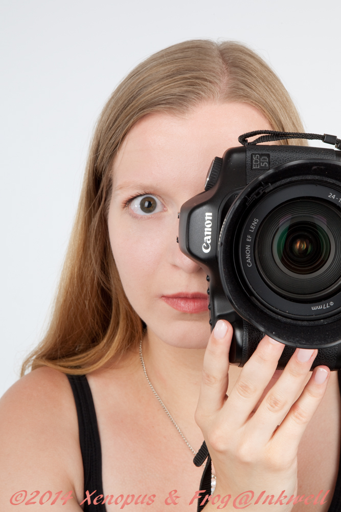 woman holding canon camera and looking into it
