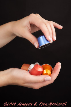 hands picking up coffee capsules