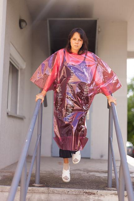 Eine Frau stützt sich mit beidem Händen auf ein Treppengelände und trägt ein pinkes Folienkleid