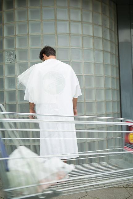 Ein Mann zeigt den Rücken und trägt einen weißen Mantel mit einer silbernen Karte eingestickt