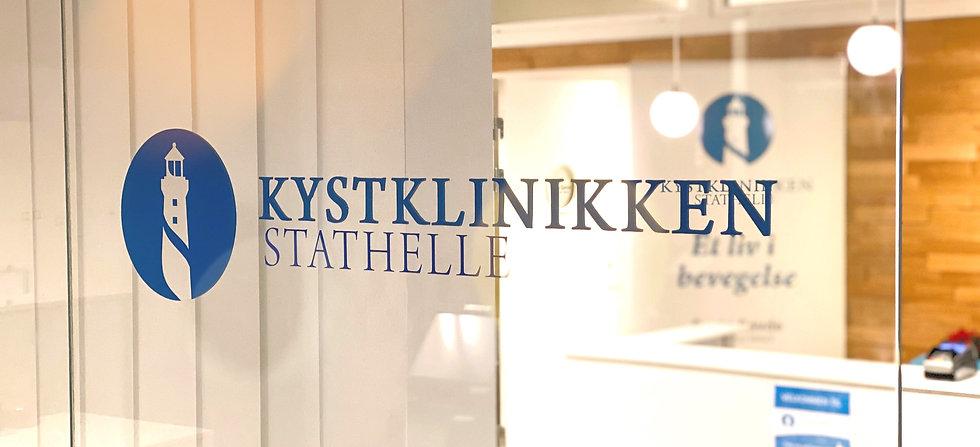 Bildet viser Kystklinikkens logo på en glassvegg med lamper og relief-vegg i tre i bakgrunnen.
