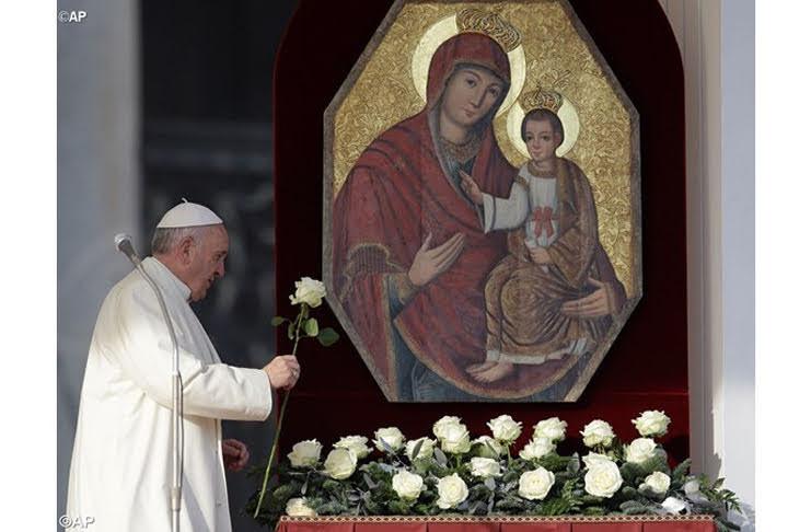 O Papa Francisco à esquerda, o ícone de Nossa Senhora com o Menino Jeus, à direita. Abaixo da Imagem, rosas brancas. O Papa retira uma e estende à imagem demonstrando devoção.