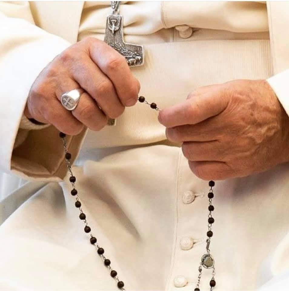 Detalhe da foto do Papa Francisco, recortando suas mãos segurando o Santo Terço em posição junto à seu Crucifixo Papal sobre sua batina branca papal.