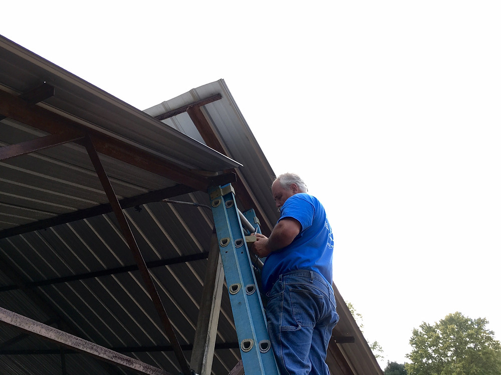 Perry measuring the truss cross supports on the existing building.