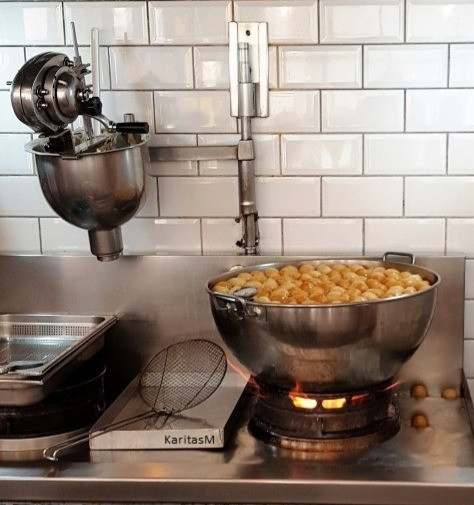 Frying a large batch of loukoumades (honey puffs).