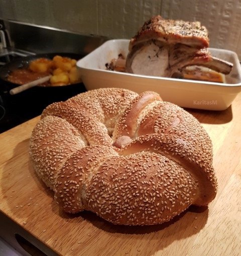 Greek Xmas Bread ready to be cut. In background pork loin resting & potatoes caramelizing