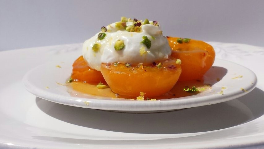 Grilled apricot halves with yogurt topping with chopped pistachios