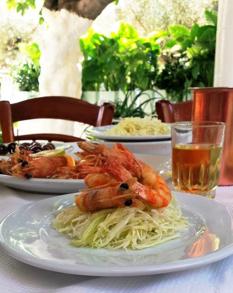Shredded cabbage salad topped with fried giant shrimp