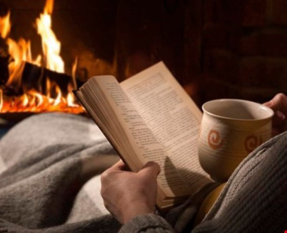 Enjoying reading a book with a hot drink