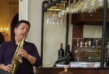 Saxophonist playing next to bar