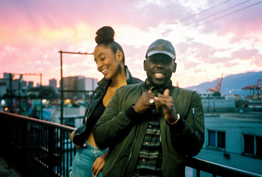 Two Black folks against a backdrop of a sunset and mountains in Vancouver