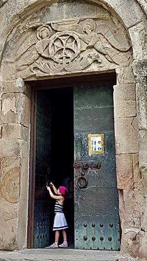 A girl stands in the doorway of Jvari Monastery in Mtskheta, Georgia