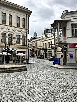 Looking down a cobblestone street in central Kutaisi with newly renovated buildings on the sides