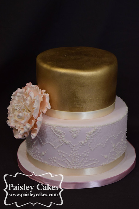 2 tiered pink and gold hand piped wedding cake