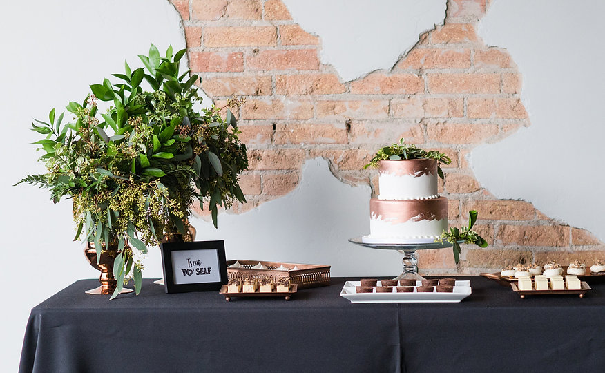 2 tiered painte copper weding cake with desserts, brick backdrop