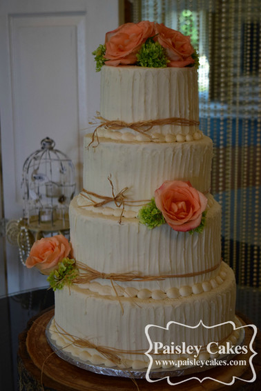 Verticle Rustic buttercream wedding cake with raffia and fresh flowers