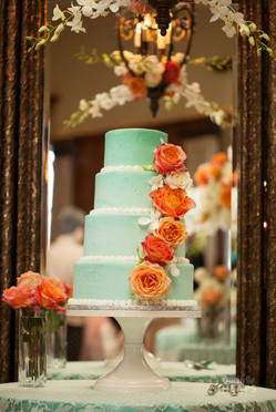 4 tiered turquoise wedding cake with fresh flowers.