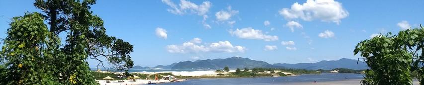 Vista da trilha para o Rio da Madre mostrando a travesia de barco até a praia da Guarda do Embaú. Foto: Acervo da Pousada  .