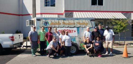 The image shows a group of volunteers standing in front of the Mobile Produce Pantry, which is parked in front of the Northside Outreach Center building.