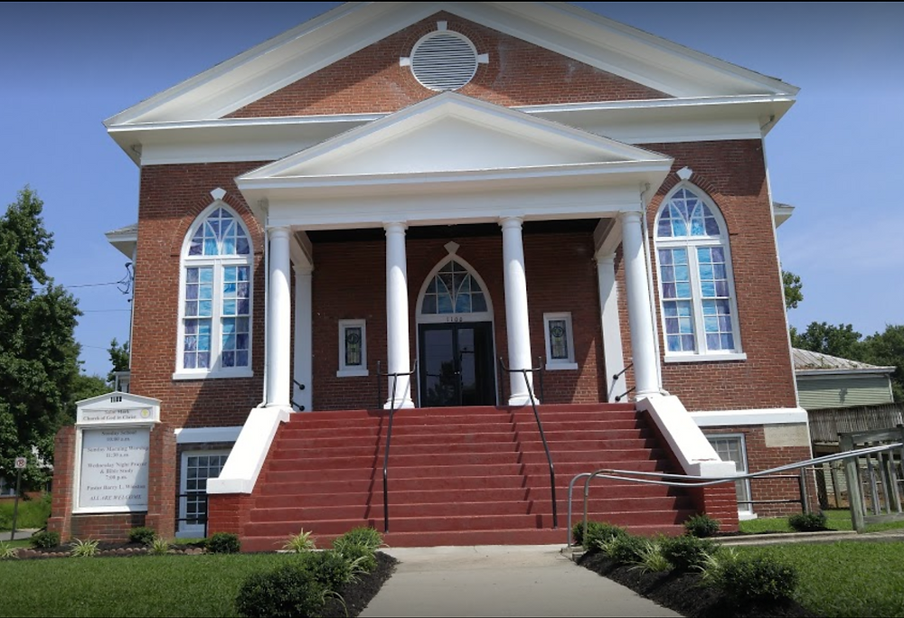 Image of St. Mark COGIC Church on a sunny day. The church is red brick with white trim and columns.