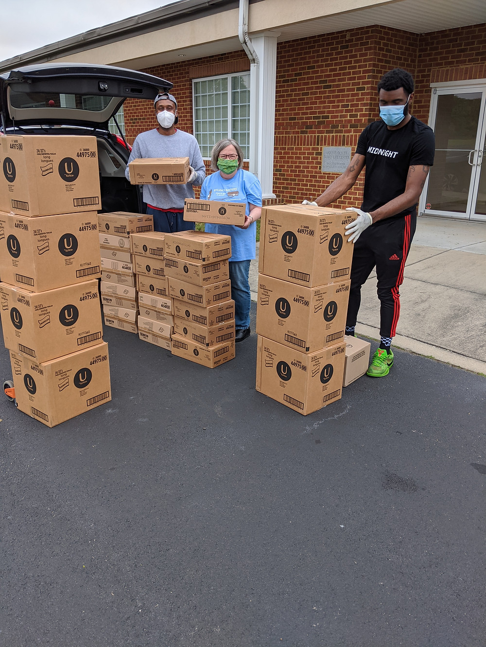 This photo shows two men receiving donation of feminine sanitary products from a female names Jennifer Taylor. They are standing in front of a vehicle parked in front of a brick building. There are large stacks of cardboard boxes displaying the Kotex logo.