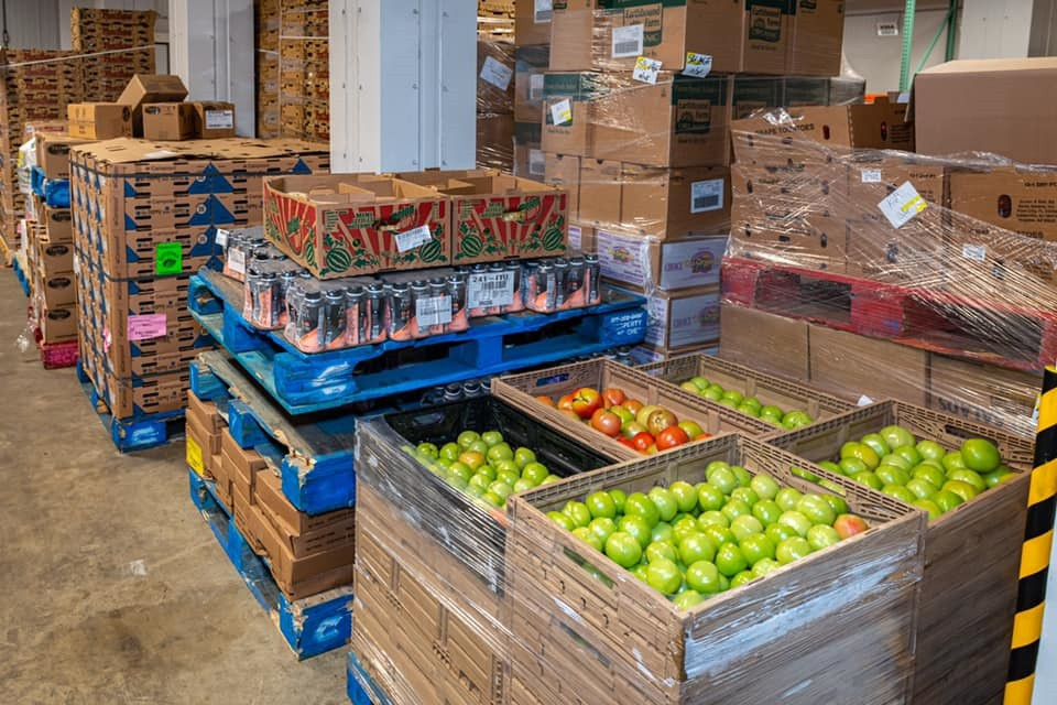 The image shows an image of pallets stacked in the Feed More warehouse. The blue pallets are positioned on the floor around white columns and display tomatoes. green apples, boxed goods, and beverages.