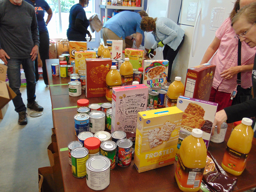 Image Shows a Table with Cereal Boxes, canned goods, and other non perishable items being packed by NOC volunteers for the monthly food pantry distribution.