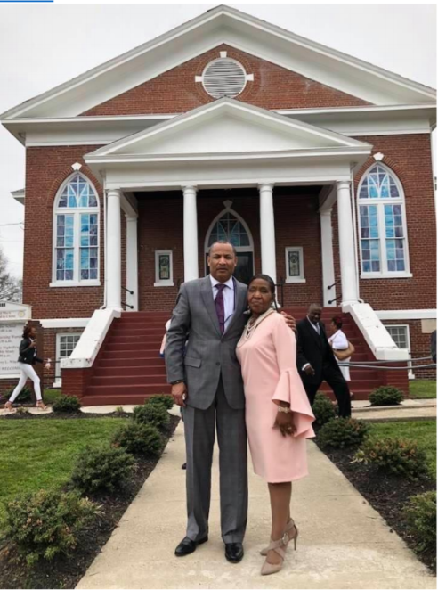 Pastor Barry L. Winston & Dollnita M. Winston stand proudly in a walkway leading towards a St. Mark COGIC. The building is a brick church with white trim and columns. There are stained glass windows with a blue glass and white crosses.