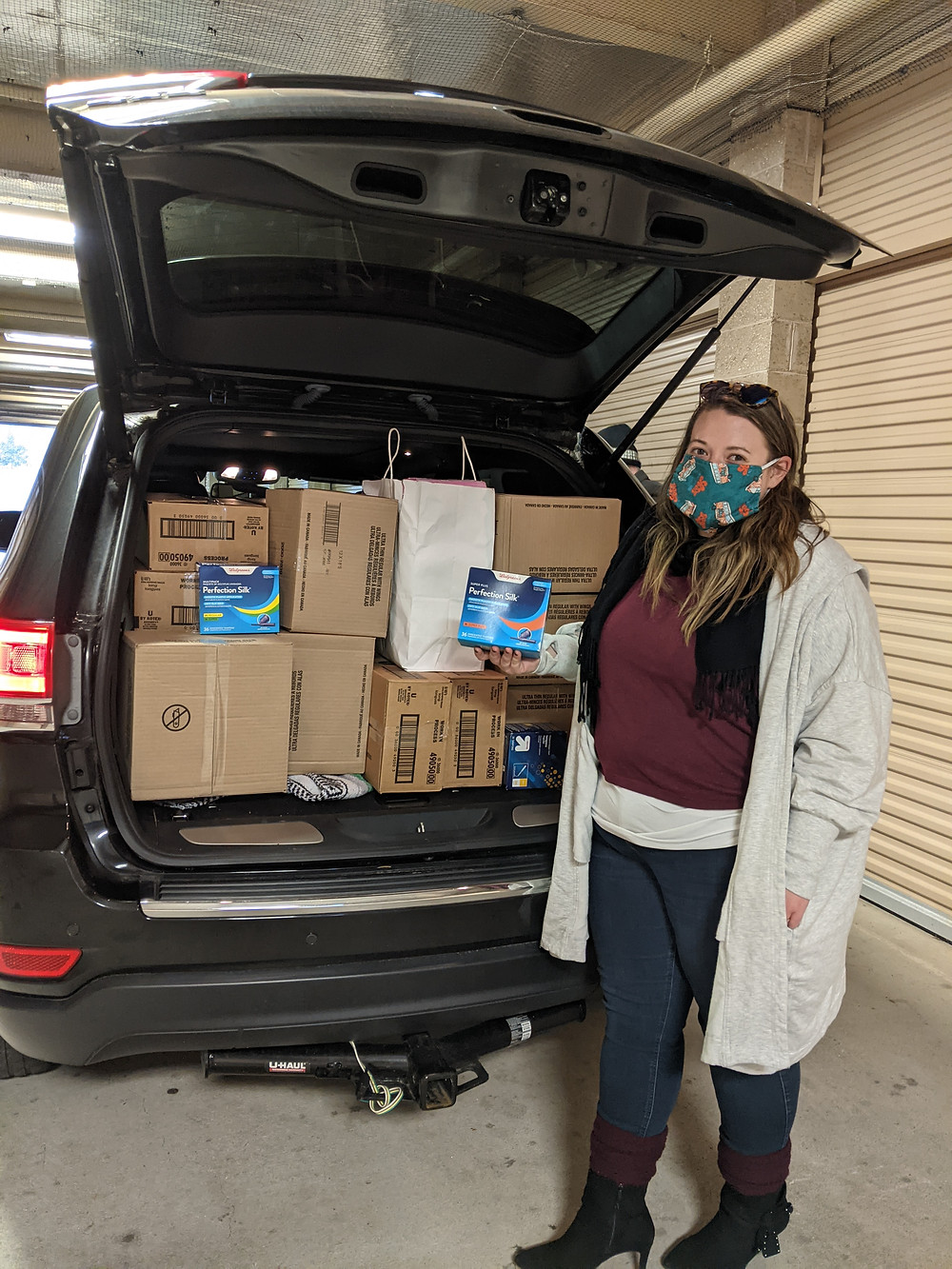 This image shows World U.P. CEO, Liz Dukette, standing in front of an open trunk which contains multiple boxes of feminine hygiene products. Liz is displaying a box.
