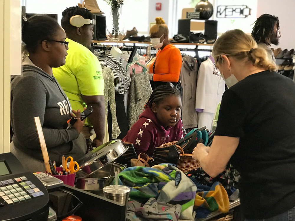 Shoppers are in the NOC thrift Center checking out at the cashier.