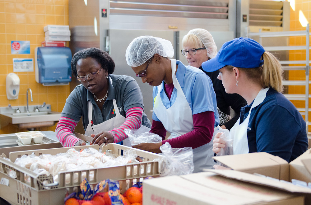 4 people stand around a kitchen  prep table loaded with food to be prepared for community meals. The kitchen walls are yellow tile and show a hand washing sink, soap dispenser, and paper towel dispenser. To the right of the paper towel dispenser is a silver restaurant quality refrigerator. The volunteers have hair nets/hats and smocks on as they plan and prep the foods.