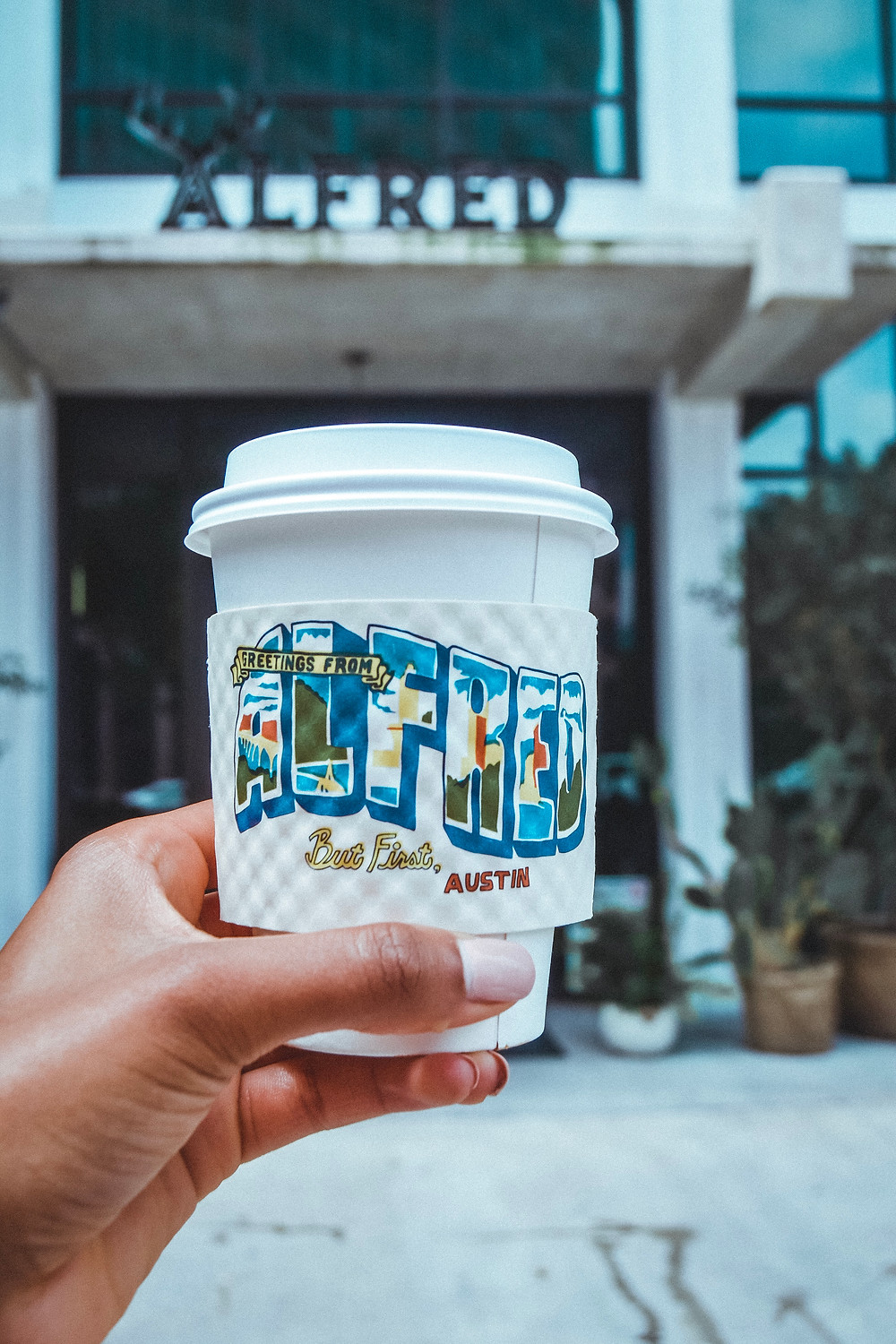 Alfred coffee with graphic coffee sleeve