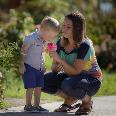 toddler with sister smelling roses