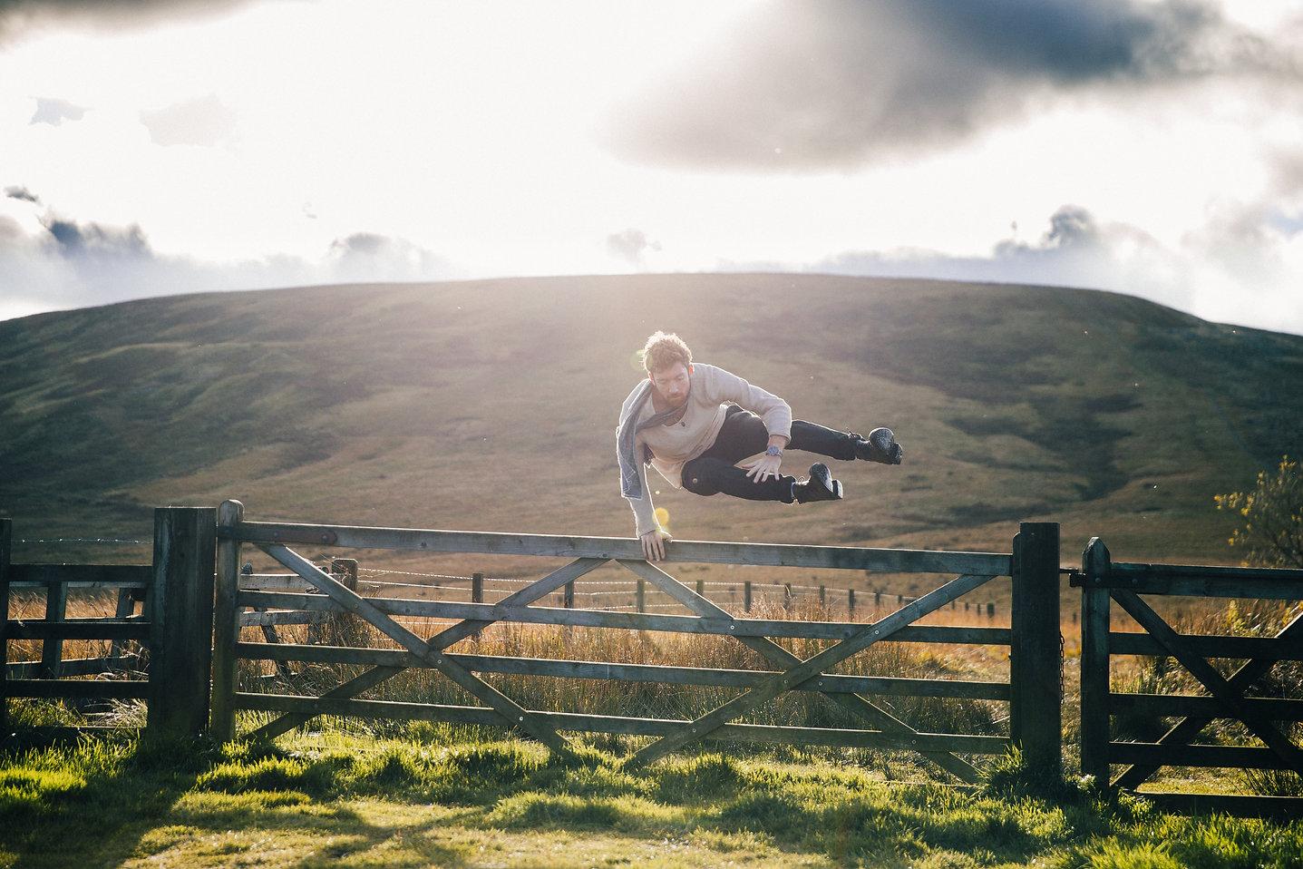 man-jumping-fence-by-field.jpg