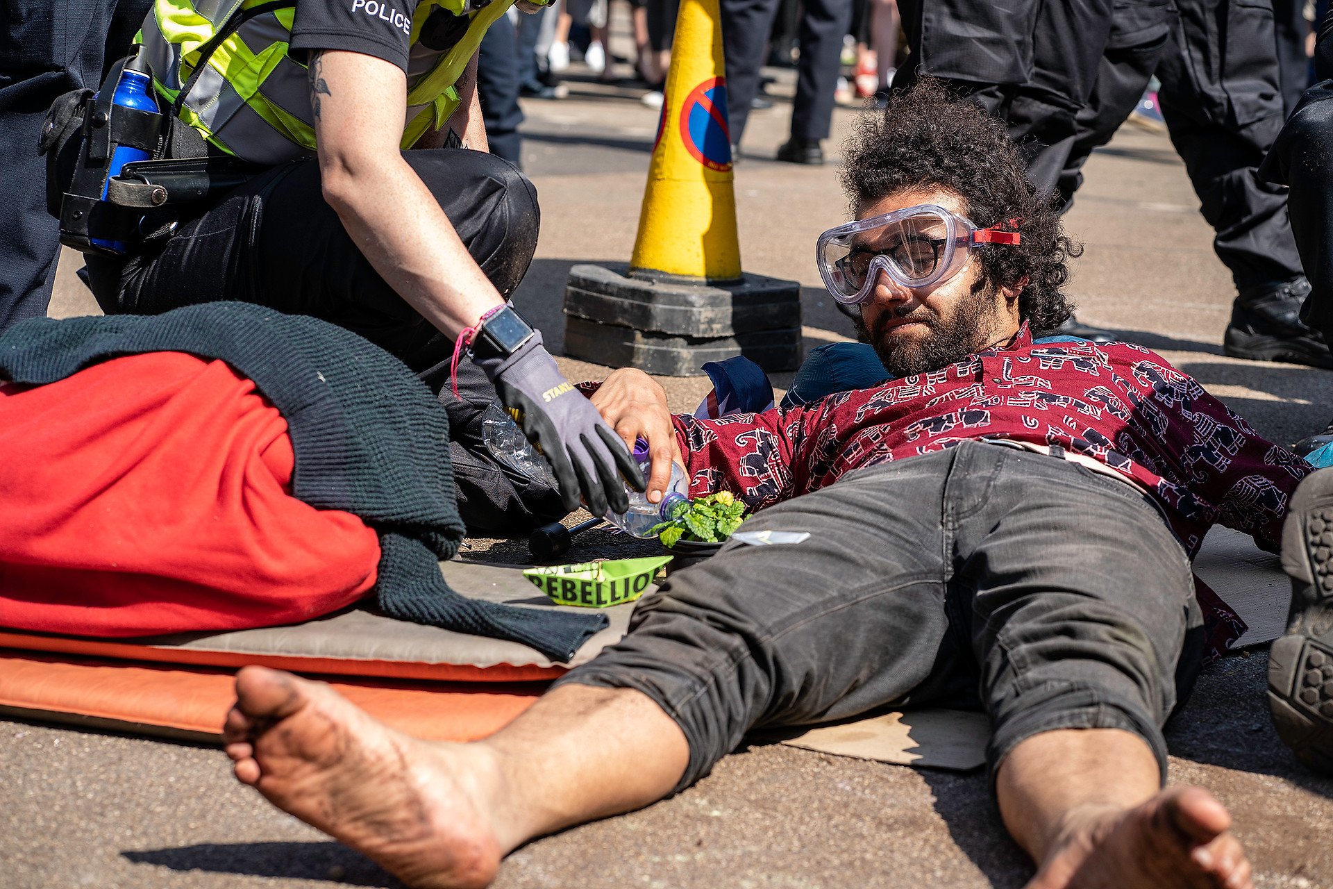 An XR arrest able waters his plant whilst chained to another protestor
