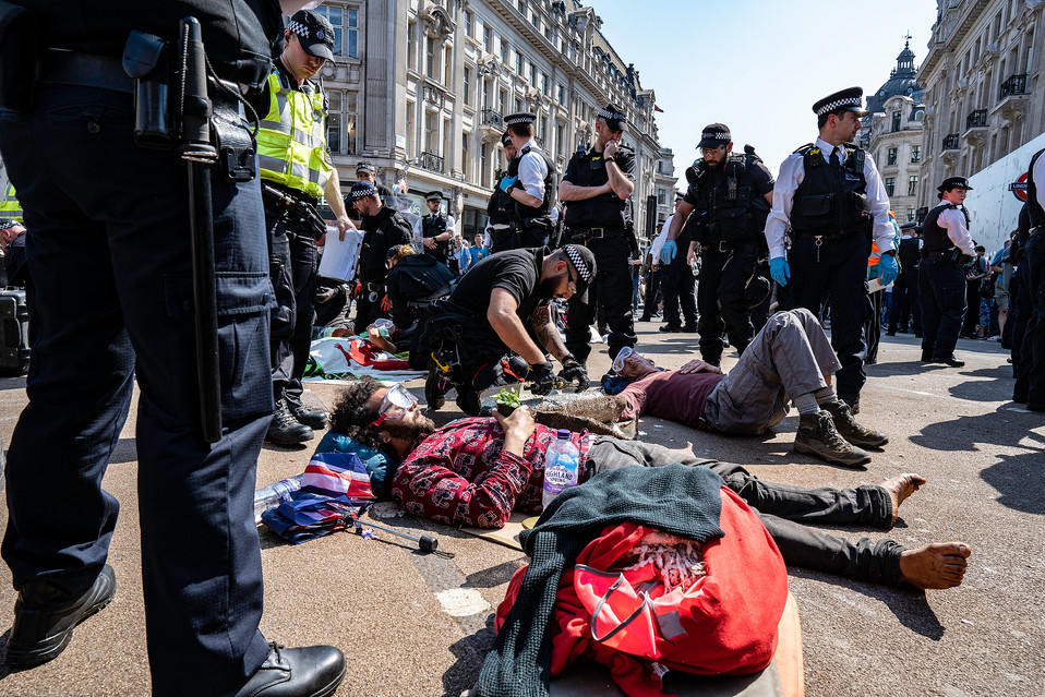 Police cut through layers of material surrounding protestors' arms in order to remove them from Oxford Circus.