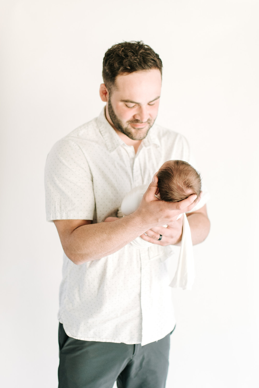 Brand new dad holds newborn son photo by Cayton Heath Photography
