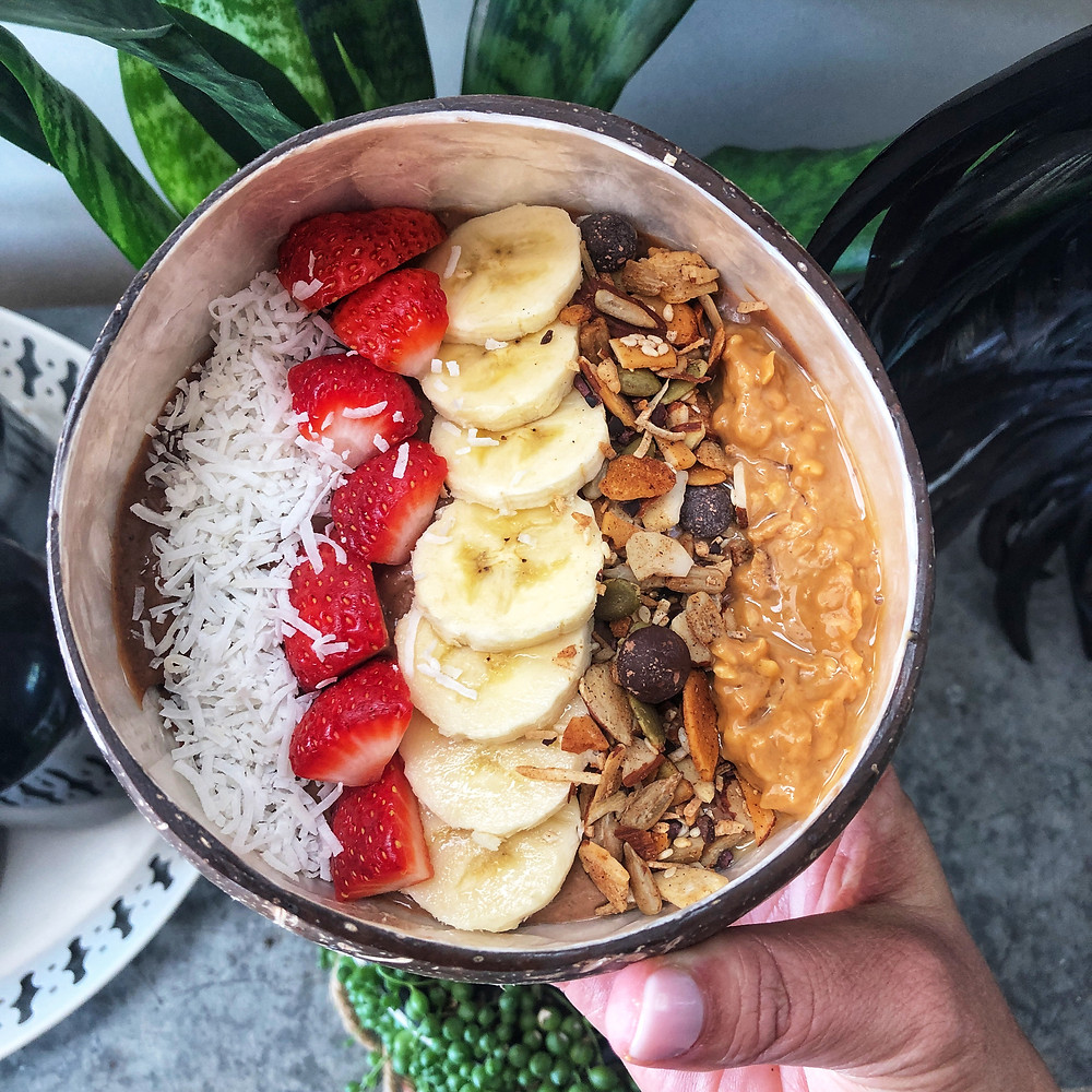 Acai smoothie bowl in a coconut shell, topped with banana, strawberries, coconut, granola and peanut butter