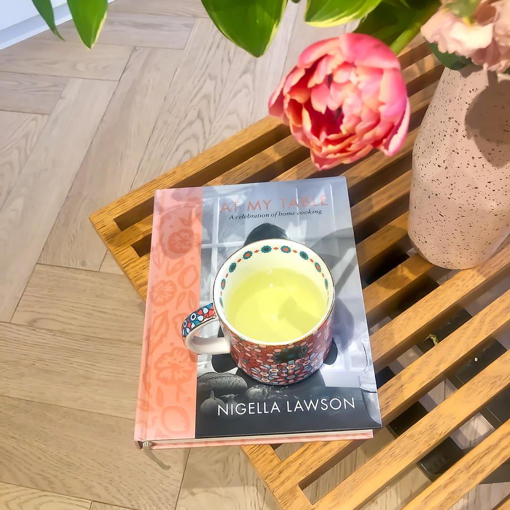 Cup of peppermint tea sitting on a Nigella Lawson book on a coffee table